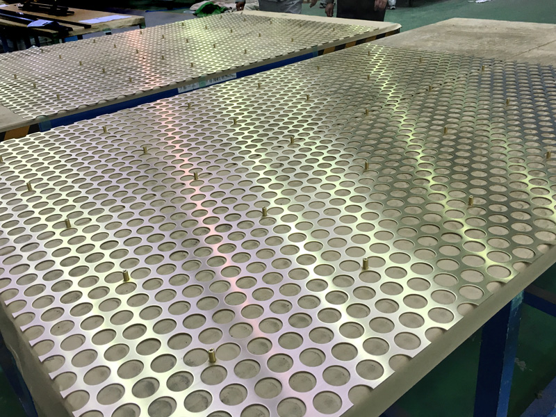 Perforated brass metal sheet before assembly.