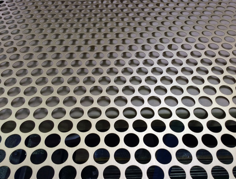 Perforated brass panel, welded vertically between the second and third perforation from the bottom left corner.