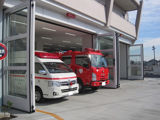Two doors consist a set of super large folding door. The opening allows a fire fighter truck and two ambulances to drive through.