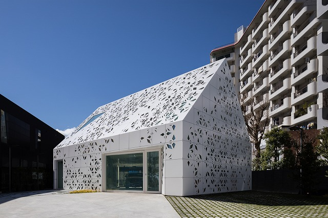 Panels with varying perforation designs cover the exterior of EQ House