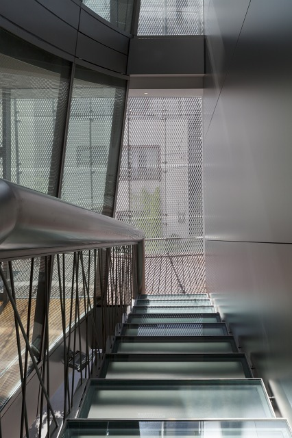 Looking down the stairs from the landing. The glass stair-boards and the see-through balustrades create a transparent space