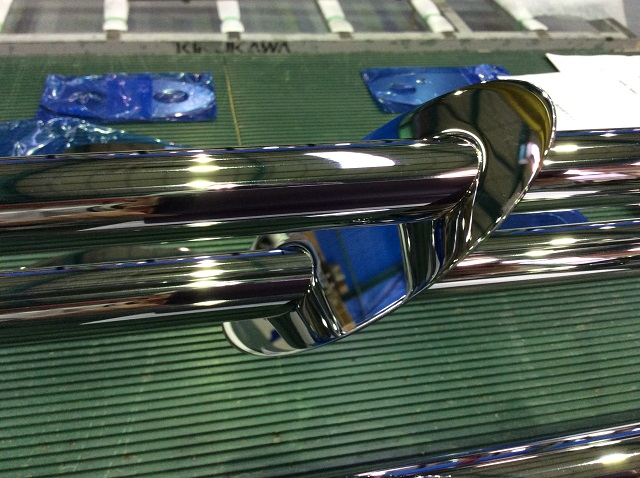 Mirror polished stainless steel oval disk and round pipe, before the coloured clear coating