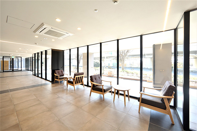 Glass-walled entrance hall, filled with natural lighting. The window frames, flush door and the automatic entrance door frames are Kikukawa metals.