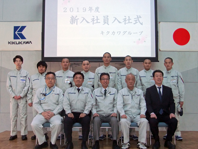 前列には当社役員、後列には新入社員とベトナム技能実習生が並ぶ記念写真