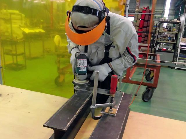 HL仕上げの研修のために、溶接したピースを仕上げる研修者