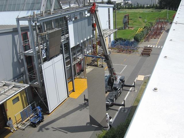 クレーンで吊るして大型SUS鏡面外装パネルを確認する様子