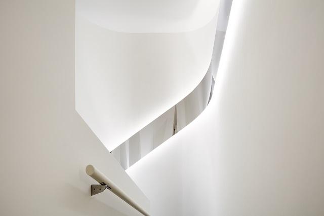 踊り場の曲面壁に沿って斜めにせり上がるステンレス鏡面リボンパネル