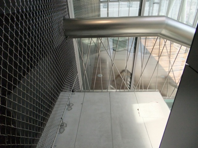 ランダムに配置された吊材が美しい透明感のある階段。