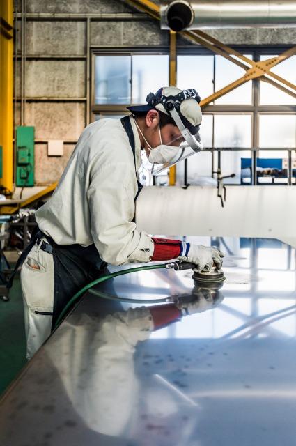 手掛けの研磨で金属素地を整える菊川の社員