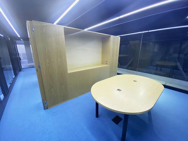 打合せスペース、反対側からの写真。カーテンのように揺らぐ鏡面ステンレスのパンチング建材とガラスが内外の空間を隔てている